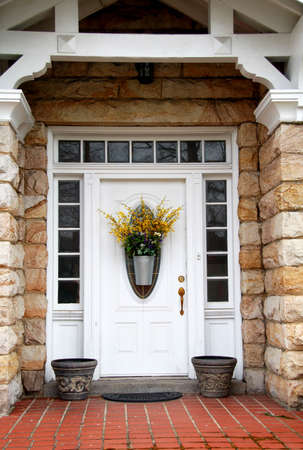 White door with transom and side lights on stone house with flower basket
