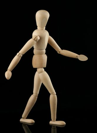 wooden figure: walking wooden figure with reflection on black background