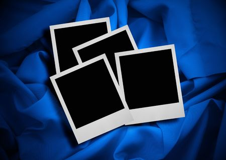 stack of photo frames against blue textile background photo