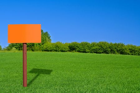 orange sign post on beautiful green meadow photo