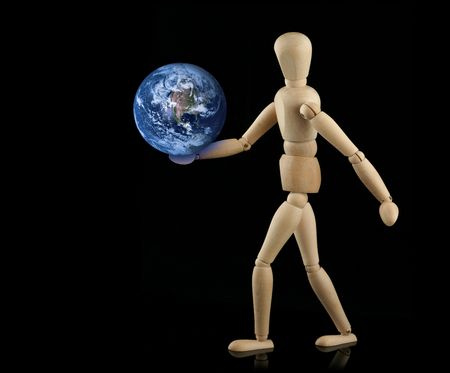 wooden figure holding glowing earth in hand photo