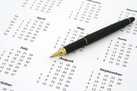 close-up of simple white yearly calendar page and ballpoint pen Stock Photo