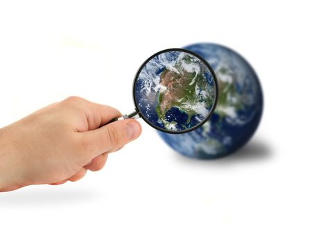 hand with magnifying glass over the globe isolated on white photo