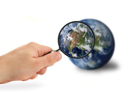 madre tierra: mano con la lupa sobre el globo aislado en blanco Foto de archivo
