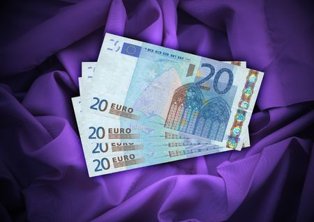 20 euro: close-up of four 20 Euro banknotes lying on satin background