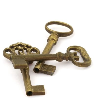 high key: close-up of three ornamented old keys isolated on white background, focus is set in foreground