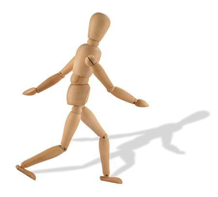 wooden figure: close-up of a running wooden figure with its shadow