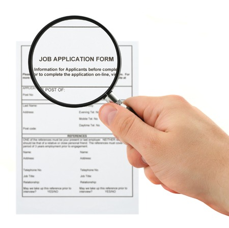 concept of searching for personnel - hand with magnifying glass and job application form