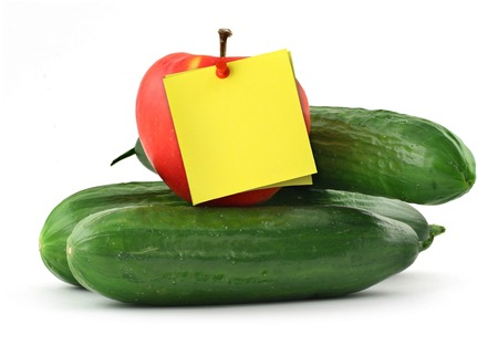 thumbtacked: cucumbers apple and blank yellow note against white background Stock Photo