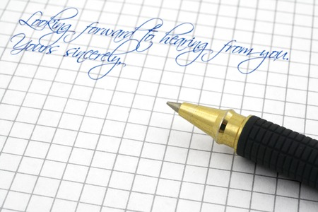 penfriend: ending of a letter on squared paper with a pen, focus is set in foreground Stock Photo