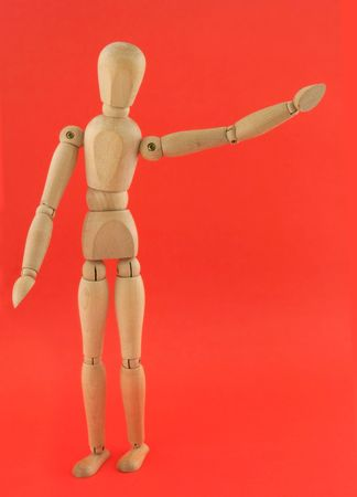 wooden figure: wooden figure in a welcoming pose on bright red background
