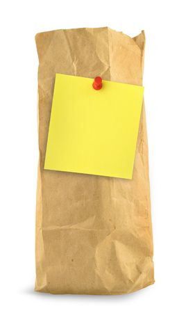 thumbtacked: brown paper bag with yellow note against white background, small shadow at the left side Stock Photo