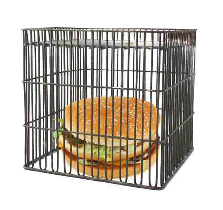 diet concept - fast food behind bars, natural shadow underneath Stock Photo