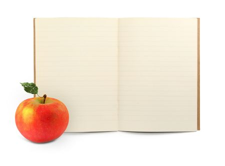 lined exercise book and apple on white, visible shadow in front photo