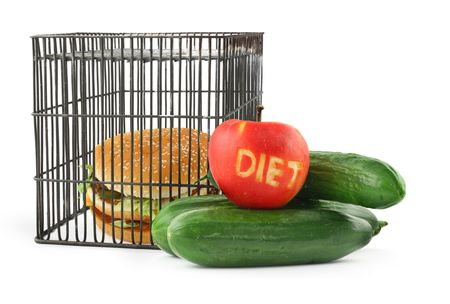 diet concept - fruit, vegetables and fast food behind bars