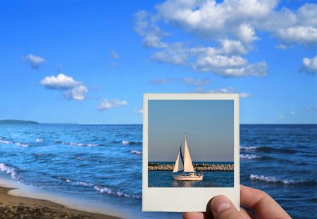 hand holding a holiday photo, beautiful seashore in background, photo inside is my property photo