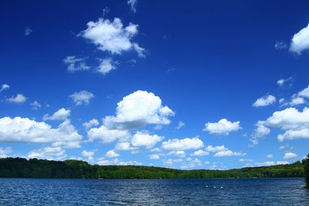 beautiful lakeside with tree line, cloudy sky above photo