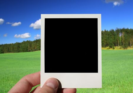 hand holding blank photo, beautiful countryside in background Stock Photo - 3296032