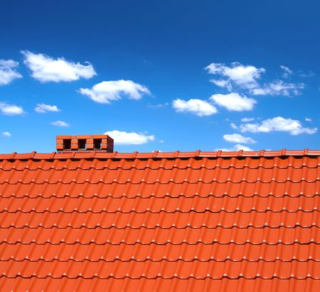 red roofing-tiles with cumulus clouds above photo