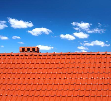 ondulation: rouge des tuiles de couverture avec cumulus au-dessus