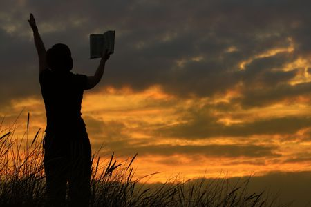 praise: female praying with bible against summer sunset, person isnt identifable Stock Photo