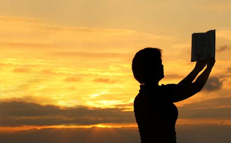 female praying with bible against summer sunset, person isnt identifable photo