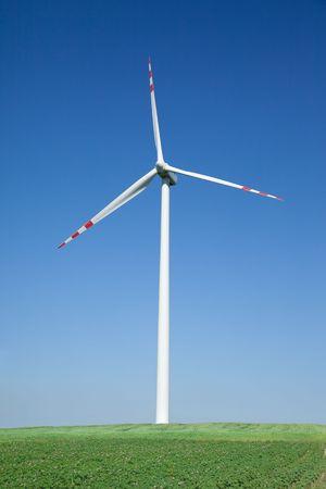 single wind turbine, cloudless sky in background photo
