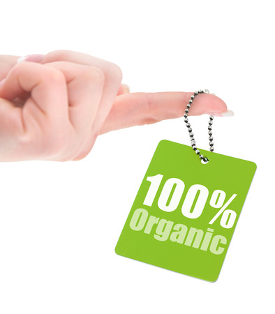 hand holding 100% organic label isolated on white background