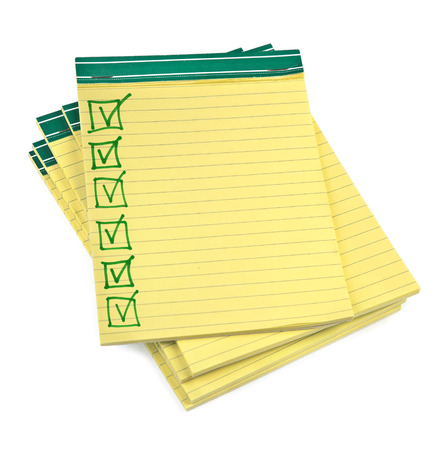 lined paper notebooks with completed checklist on white background photo