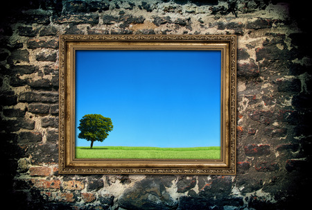 golden wooden frame with beautiful landscape over ruined brick wall. photo