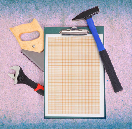 Clipboard with graph paper and tools over rough background photo