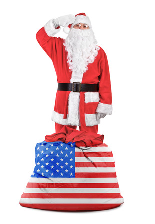 Santa claus with american sack salutes over white background photo