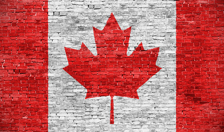 canadian icon: Canadian flag over old brick wall Stock Photo
