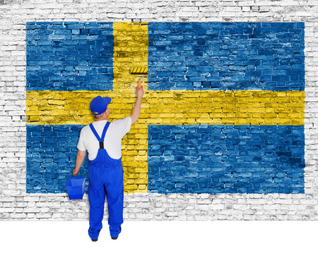 Professional house painter covers brick wall with flag of Sweden photo
