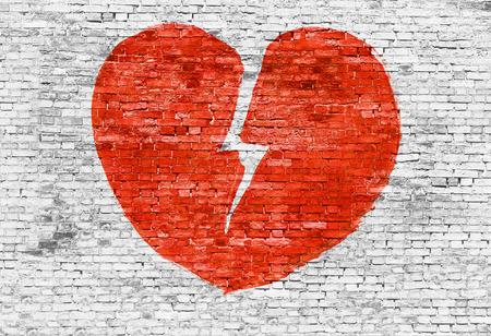 corazon roto: Roto el coraz�n pintado en la pared de ladrillo blanco Foto de archivo