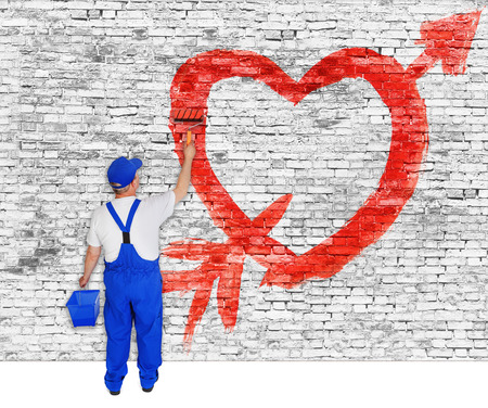 Heart and arrow painted on white brick wall by man photo