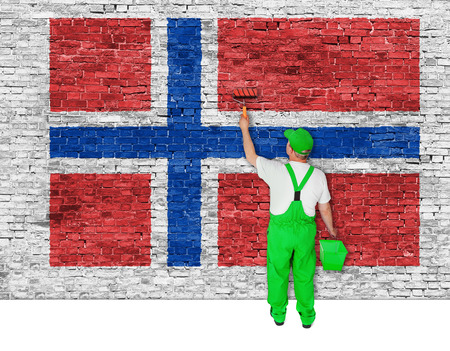 house painter: house painter covers brick wall with flag of Norway Stock Photo
