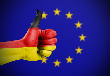 thumbup: Flag of Germany painted on hand aganinst European Union flag