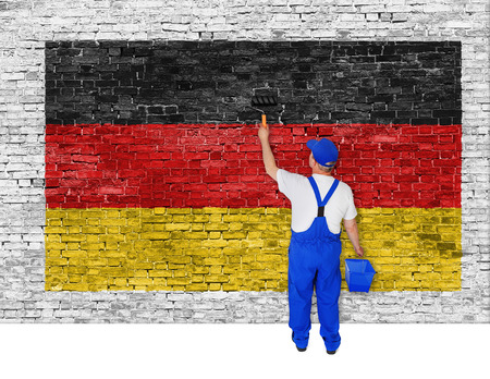 ruined house: Painter covers white brick wall with flag of Germany Stock Photo