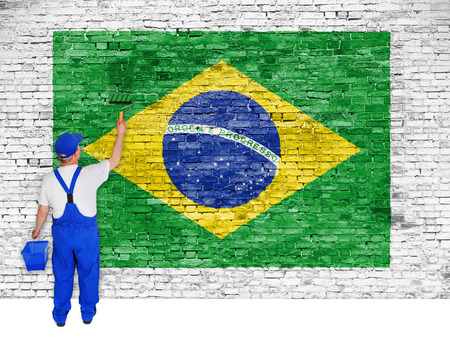 House painter covers white brick wall with flag of Brazil photo