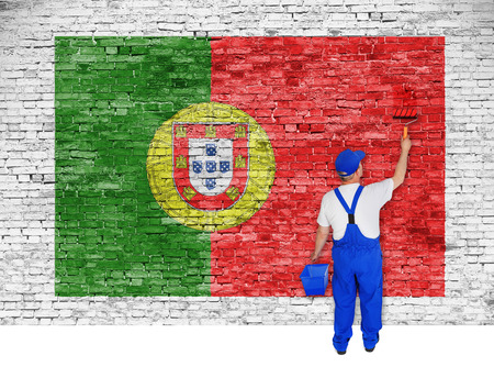 house painter: house painter covers white brick wall with flag of Portugal Stock Photo