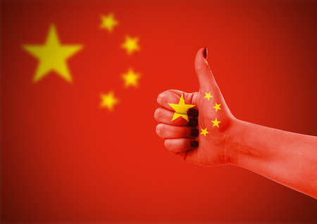 red flag up: National flag of China on female hand Stock Photo