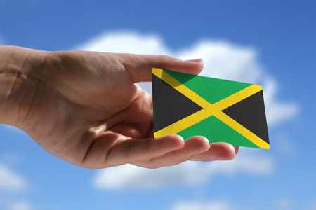 jamaican flag: Small Jamaican flag against sky with cumulus clouds
