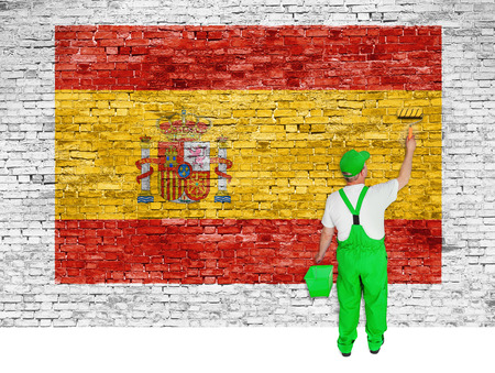 house painter: House painter paints flag of Spain on white brick wall