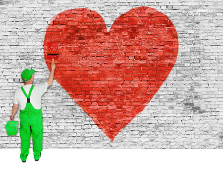 house painter: House painter paints symbol of broken love on white brick wall Stock Photo