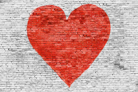 red paint: Symbol of love painted on white brick wall Stock Photo