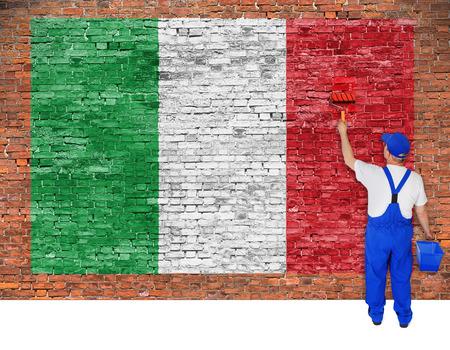 italian fresco: House painter paints flag of Italy on old brick wall Stock Photo