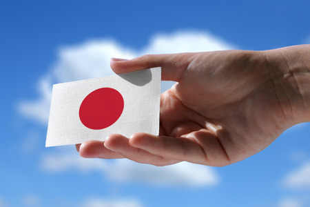 bandera japon: Peque�a bandera japonesa contra el cielo con nubes c�mulos