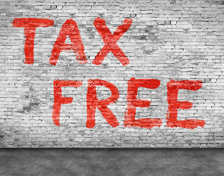 reduce taxes: Tax free painted over white brick wall