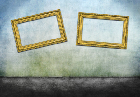 crooked: Two crooked golden frames on gray dirty wall
